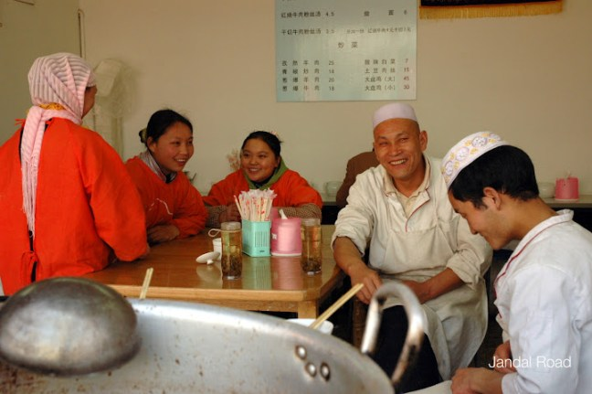 Friendly chefs and waiting staff in a street restaurant in Nanjing