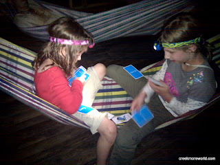 The girls play cards in the hammock at night.