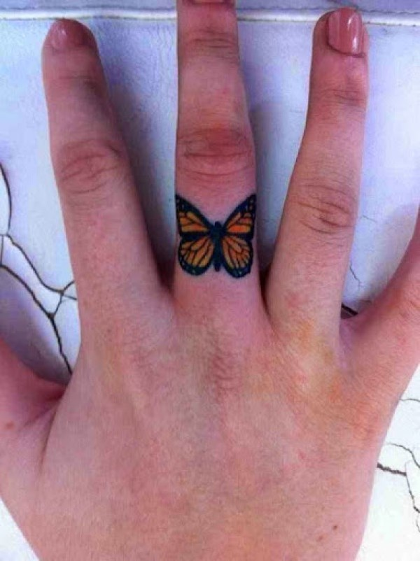 small butterfly tattoo on finger
