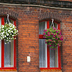 Typical Silesian view - colorful flowers on red painted windows of a brick house.