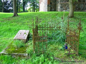 Żeliwny płotek i nagrobek z dawnego cmentarza przykościelnego w Kołowie (fot. Agata Freindorf, 2014 r.)