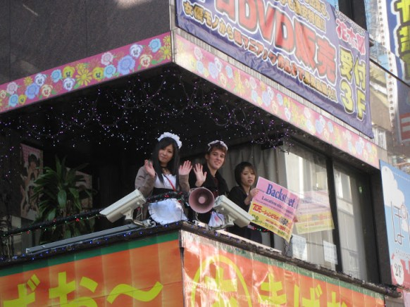 Maids waving from the balcony of the maid cafe