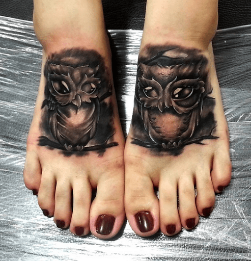 Two matching black ink use owl tattoo on feet