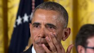 President Barack Obama wipes away tears from his eyes as he speaks in the East Room of the White House in Washington, Tuesday, Jan. 5, 2016, about steps his administration is taking to reduce gun violence. Also on stage are stakeholders, and individuals whose lives have been impacted by the gun violence. (AP Photo/Carolyn Kaster)