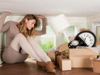 Young woman with box of objects in small room