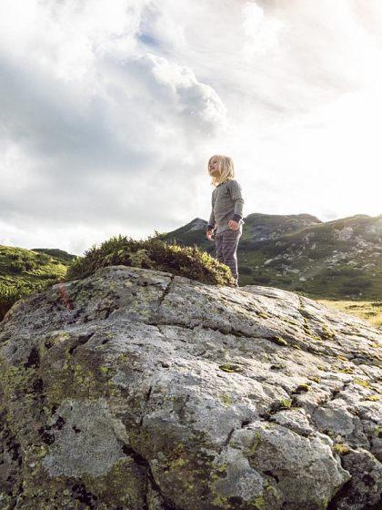 LIFEforFIVE-Wandern-mit-Kindern Kind mit Wollunterwäsche auf grossem Felsen.