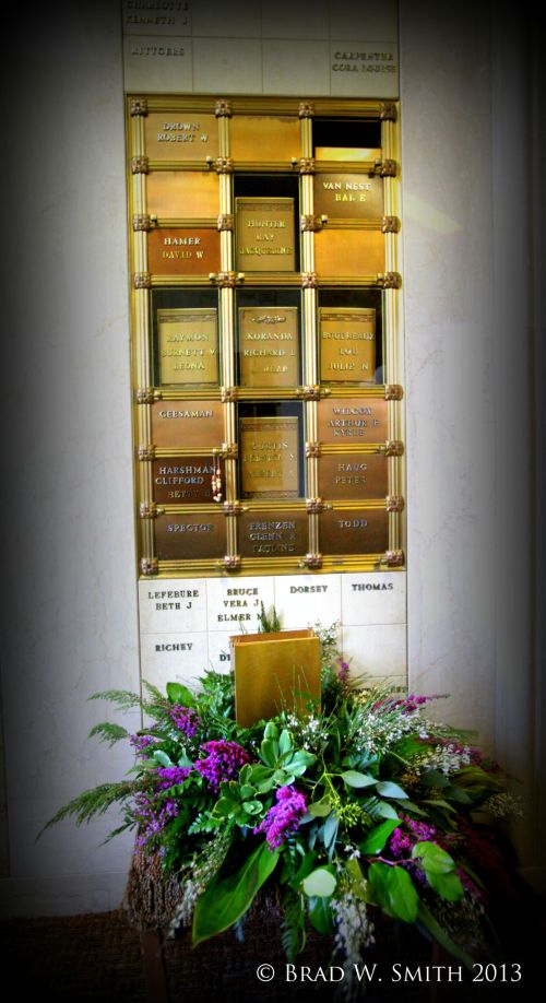 An indoor columbarium niche wall of recessed compartments holding urns.