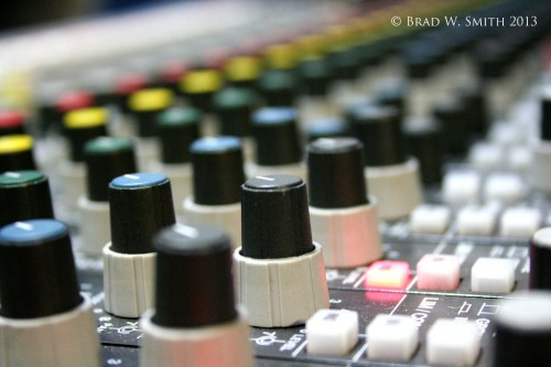 rows of knobs on an audio recording mixing console