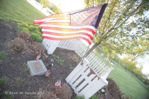 American flag, cenotaph marker, white picket fence, backlit by sun