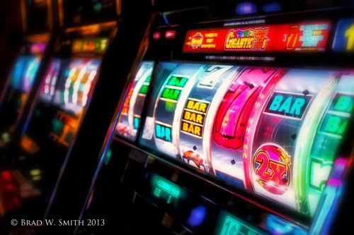 one-armed bandit in a casino with four rolling drums of images, in a sea of bright flashing neon casino lights