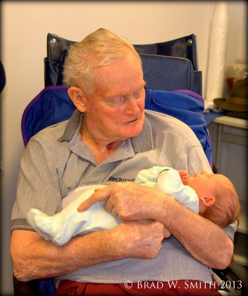 an elderly man in wheel chair in a nursing home, holding a sleeping newborn