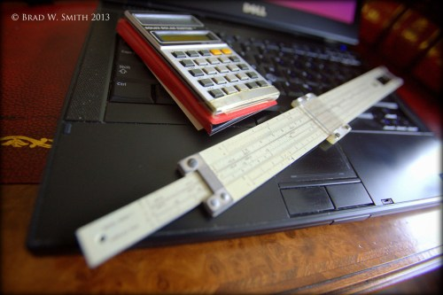 close up of slide rule, calculator and laptop on a antique desk