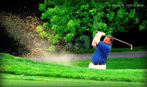 male golfer hitting a ball out of sand trap, sand spraying widely, terrible form