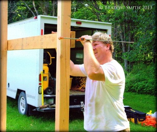 White man building a wood framework for sandbox with playhouse over the top. Utility truck in background. Backyard grass and trees.
