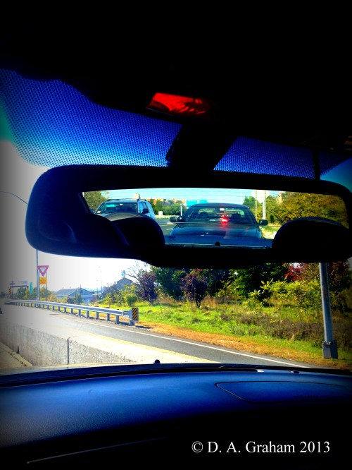 from inside the car, view of state trooper's car behind, on interstate shoulder