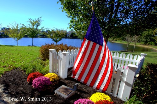 American flag, white fence, small headstone, pots of mums in purple, yellow and orange.