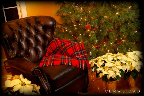 empty leather chair, red plaid blanket, next to Christmas tree