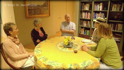 five middle-aged white men and women, yellow tablecloth, filled wood bookshelves