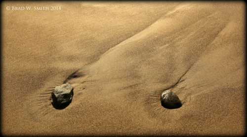 brown sand, two small stones of equal size about 2 feet apart, each with a dark trail from receding water.