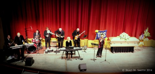 large stage flanked by full length red velvet drapes, closed casket, band, singer at mic
