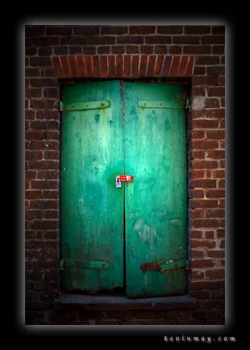 green door padlocked, red brick wall