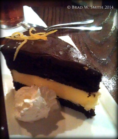 3 layer cake of white and dark chocolate with chocolate ganache,  on plate with whipped cream, in a nice restaurant