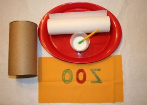 Image shows a tray with watered down glue and a paint pen next to a canister and a piece of yellow fabric with ZOO on it upside down.