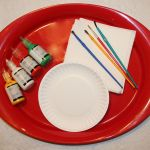 Image shows a tray with 4 bottles of fabric paint, a paper plate, 4 paint brushes, and some paper towels on it.