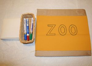 Image shows some paper towels and a tray with 3 paint pens in it next to the fabric with the word ZOO outlined on it.