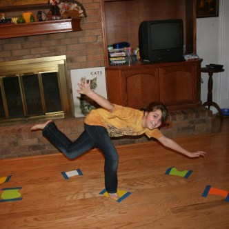 Image shows a girl balancing on paper shapes taped to a floor to make an imaginary stream.