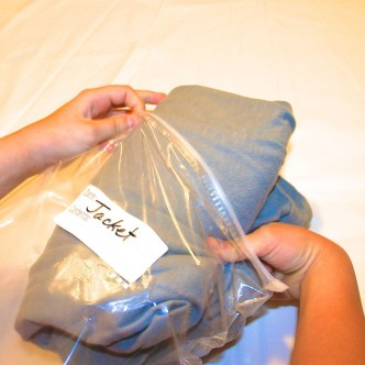 Image shows a child packing a jacket in a plastic bag.