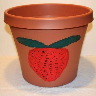 Image shows a large plastic, clay-colored pot with a child's painting of a strawberry on it.