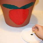 Image shows a child using a toothpick to pick up some black paint for use on a strawberry pot.