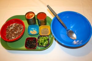 Image shows a green tray with browned meat & onions, 2 cans of tomato sauce, Italian seasoning, garlic, black olives and green peppers next to a large mixing bowl and spoon.
