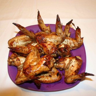Image shows a purple plate with large marinaded cooked chicken wings on it.