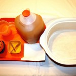Image shows a red tray with a gallon of apple juice, a cup of orange juice, a clove-encrusted orange resting in a small bowl, a small bowl with two sticks of cinnamon in it, and some paper towels. The tray is next to a large ceramic pot.