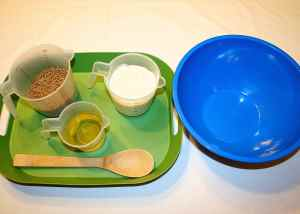 Image shows a green tray with measured All-bran cereal, yogurt, oil and a wooden spoon on it next to a large blue bowl.