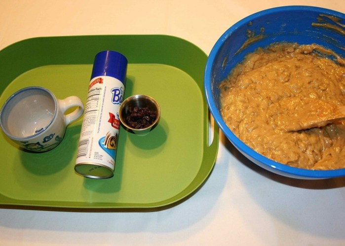 Image shows a green tray with a coffee mug, a can of floured cooking spray and some raisins on it next to a large bowl with batter and a spoon in it.