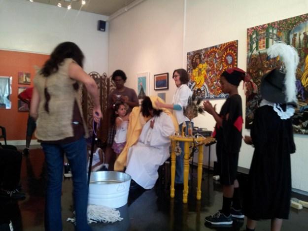 Audience member (Raksha Parekh), wearing a burlap smock, mops the floor, portraying Babalu Ayé.