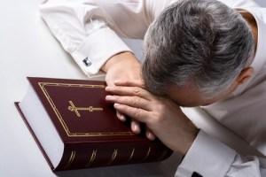 Photo of sad old man praying to God with Bible