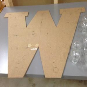treplate utskjært bokstav med lys