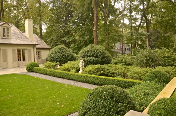 A gravel path lines the lawn and boxwood hedges