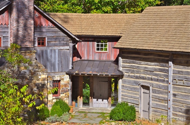 The two log cabin 'wings' are joined by this red barn wood entry