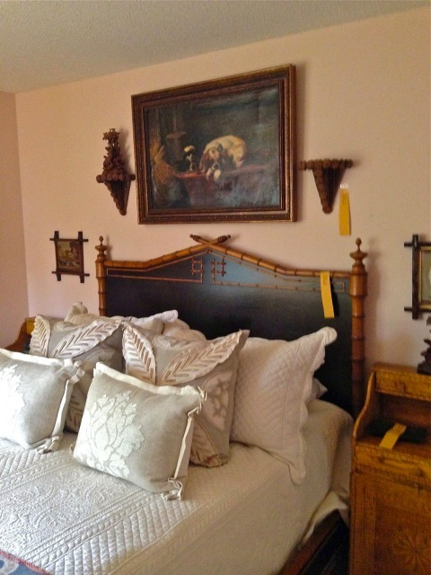 Faux bamboo bed is surrounded by brackets made from pine cones, paintings and small framed needlepoint landscapes