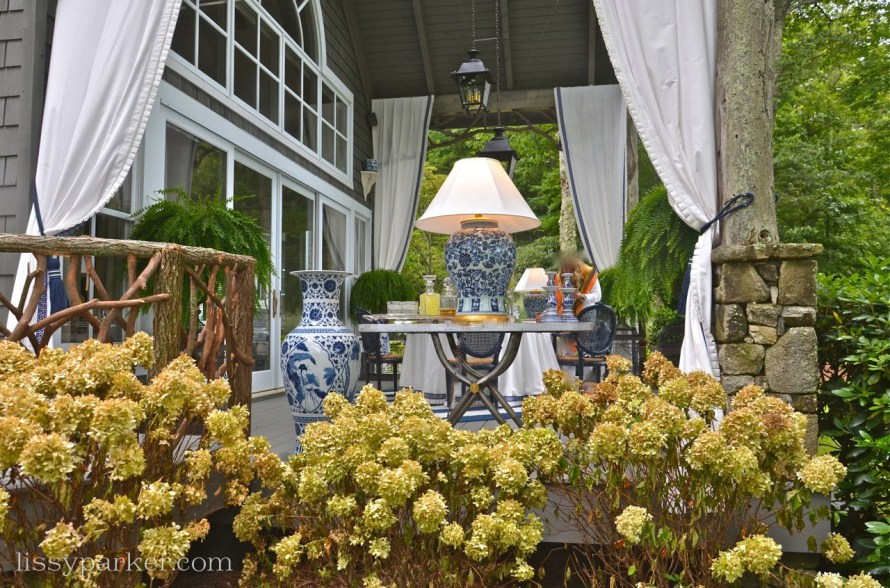 Hydrangeas line the side of the porch—blue & white lamps add to the intimate setting