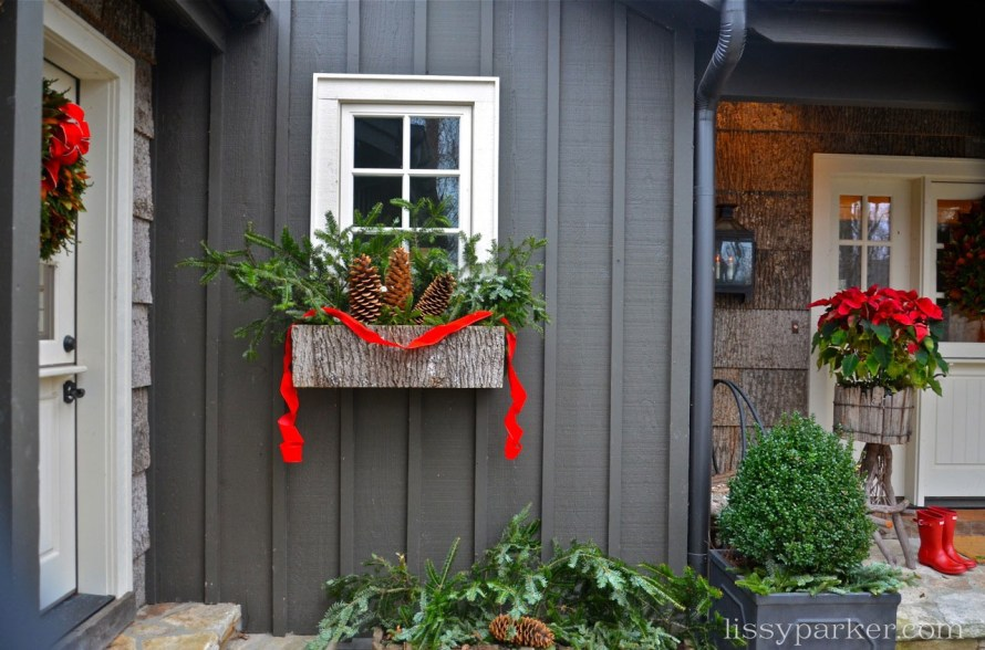 large pine cones and branches decorate the window box