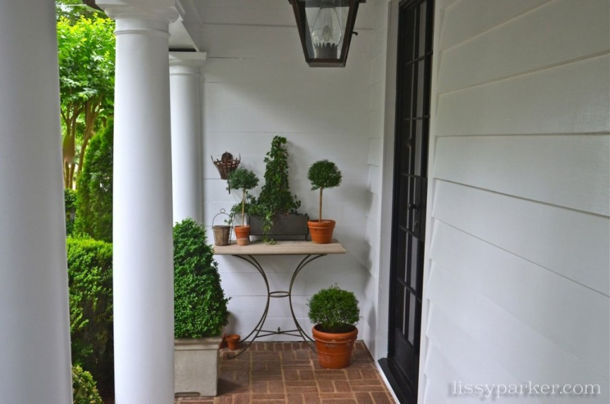 Small porch leads to another boxwood filled garden