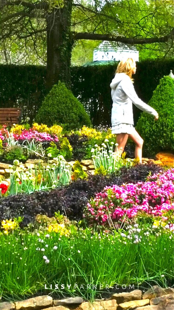 Actor walking through flower garden