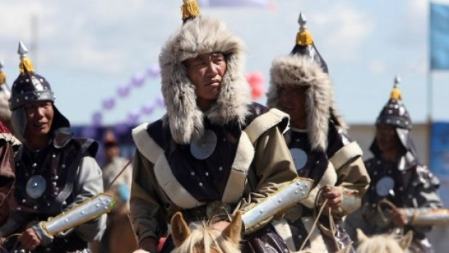 Mongolian horsemen ride in formation during opening ceremony of annual Naadam festival in Arvaikheer
