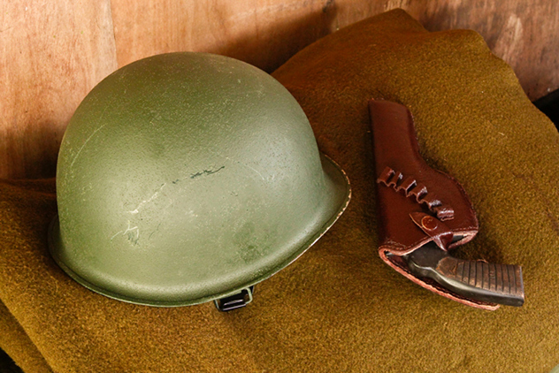 Military helmet and revolver on blanket